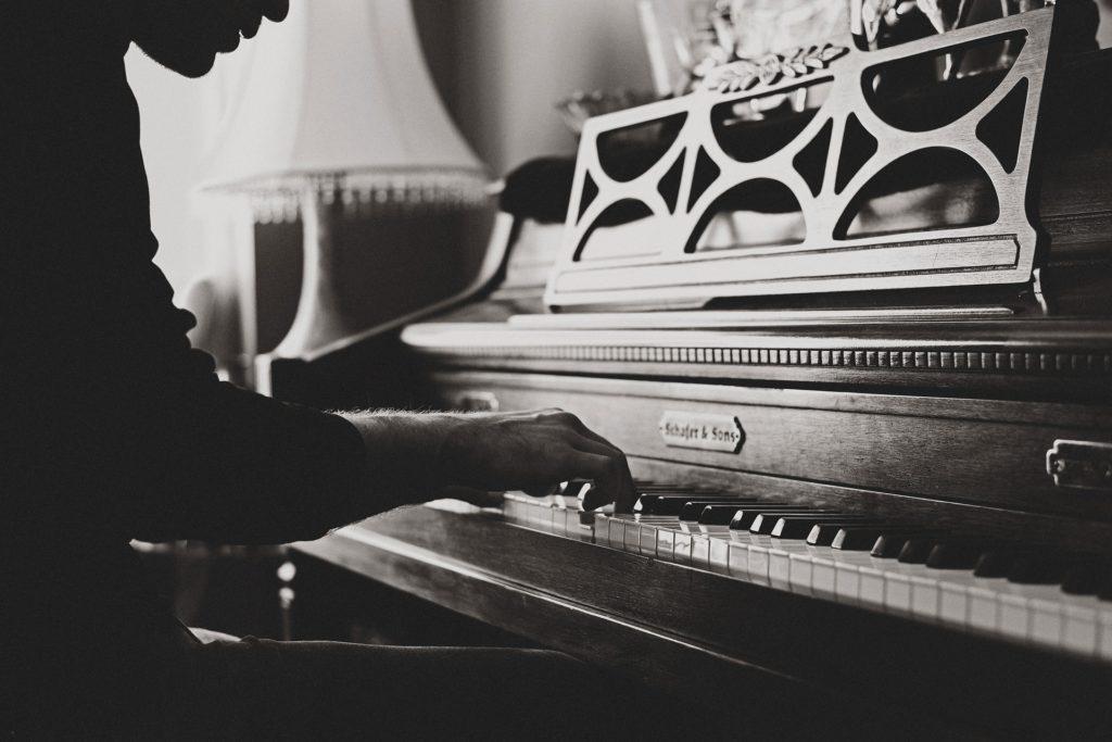 Imagen en blanco y negro: una persona toca el piano.