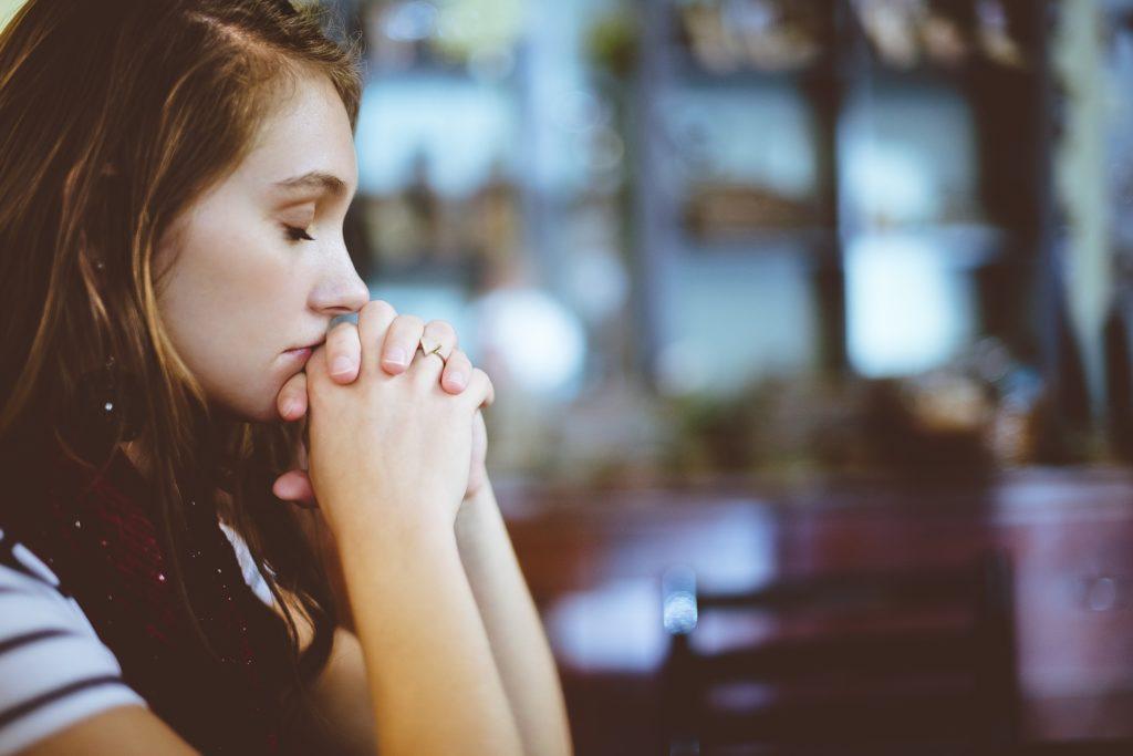 Una chica de perfil con los ojos cerrados y las manos entrelazadas a la altura de la boca