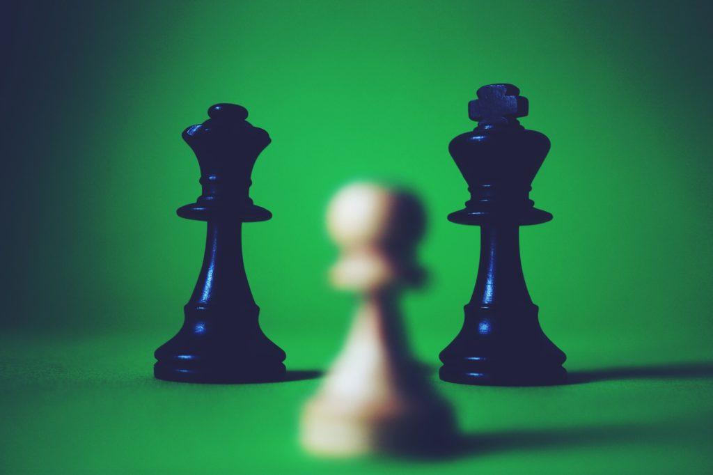 Un peón blanco frente a dos figuras negras, una la reina y otra el rey.