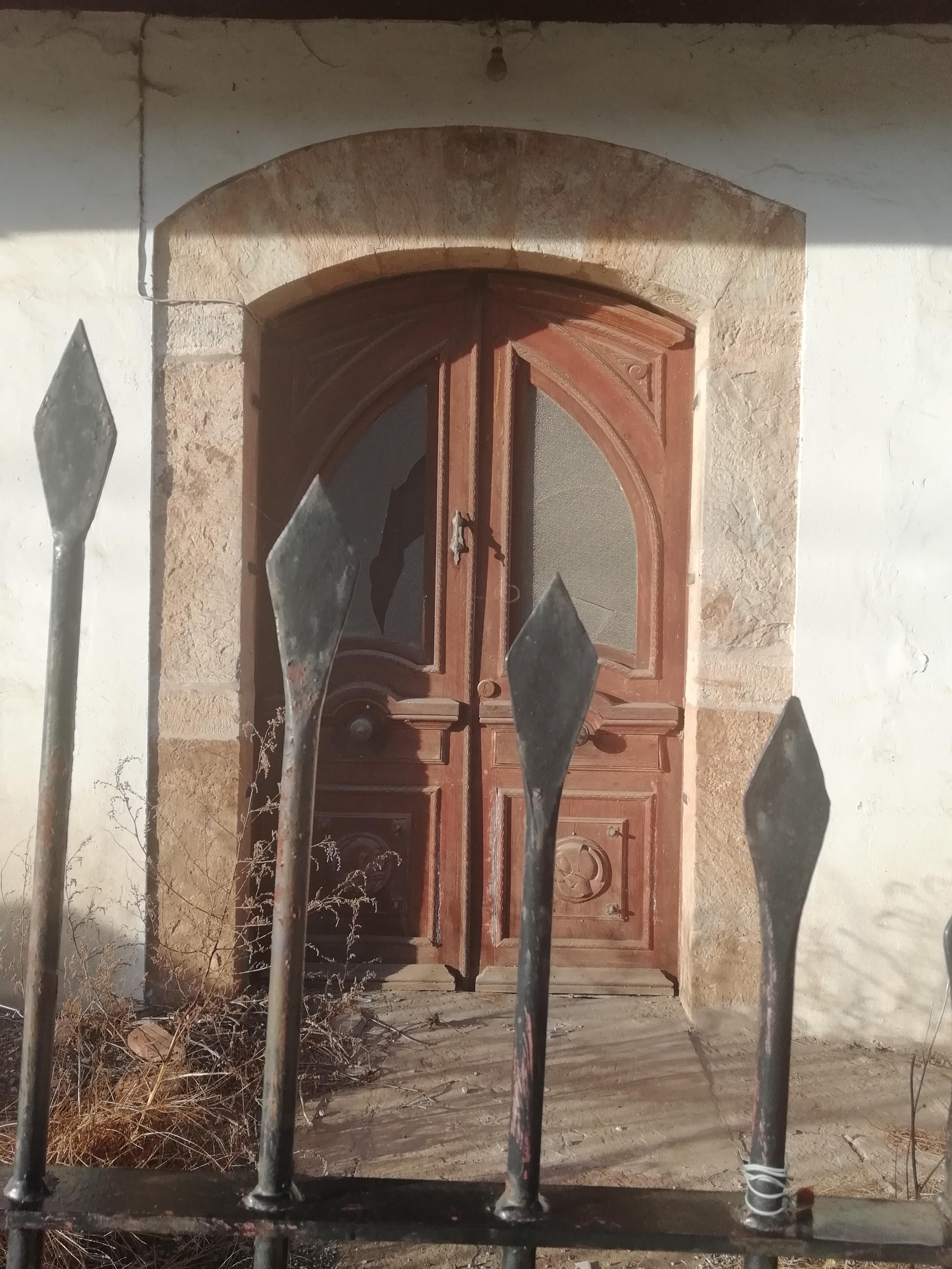 En primer término, una verja. En segundo, una vieja puerta de dos hojas con los cristales rotos.