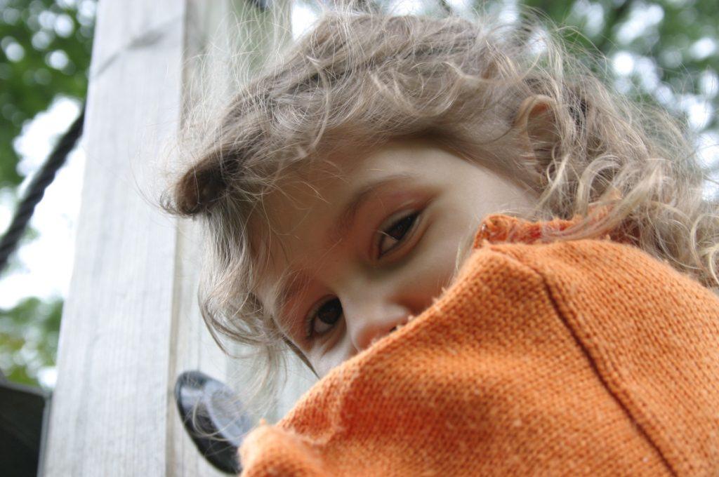 Una niña de pelo rizado rubio mira a cara sonriente. Sólo vemos la parte superior de su cara. Lleva un suéter naranja.