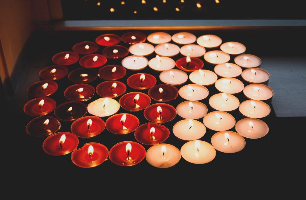 Un símbolo del Yin y el yang hecho con velas oscuras y blancas encendidas