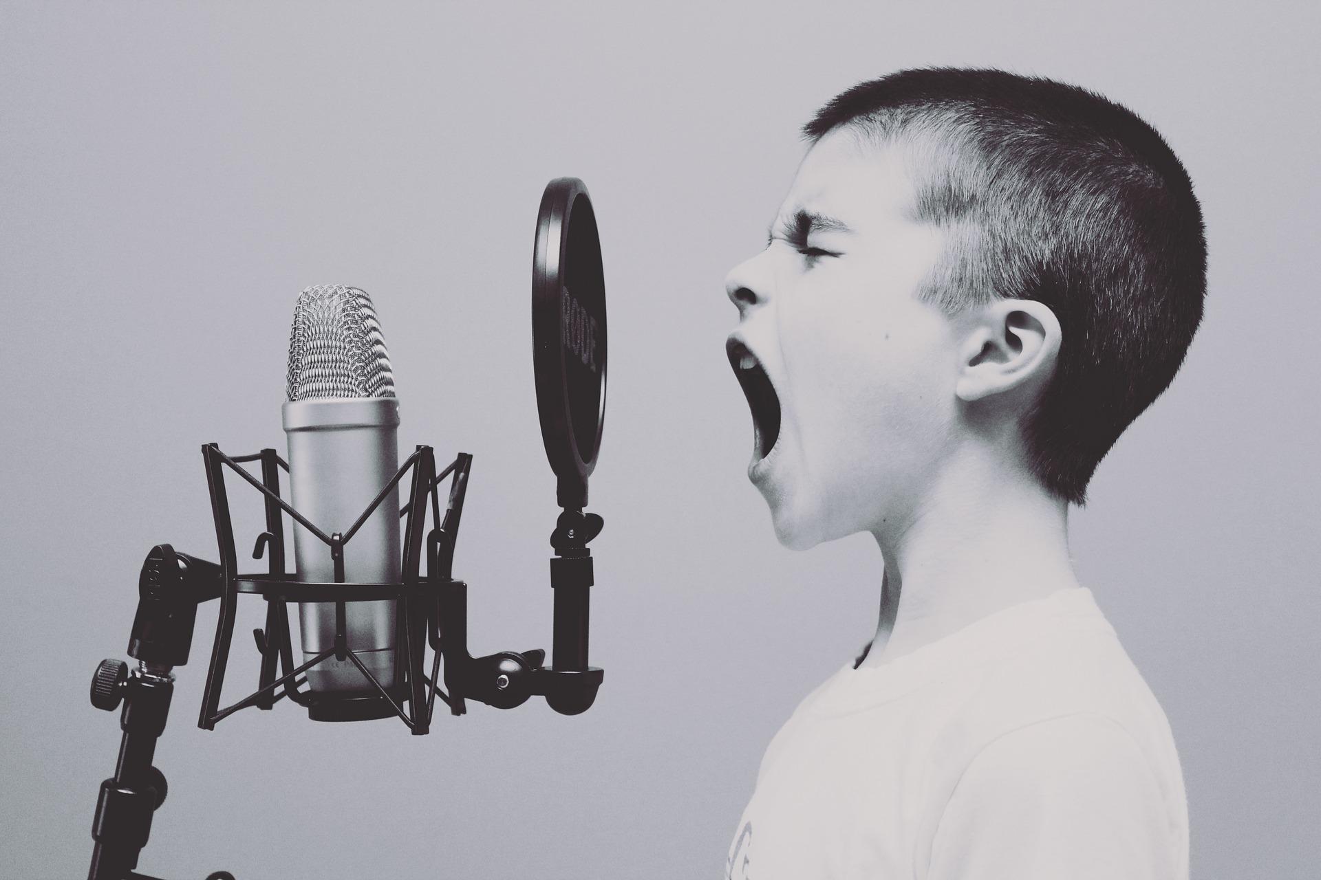 Un niño o niña grita delante de un micrófono