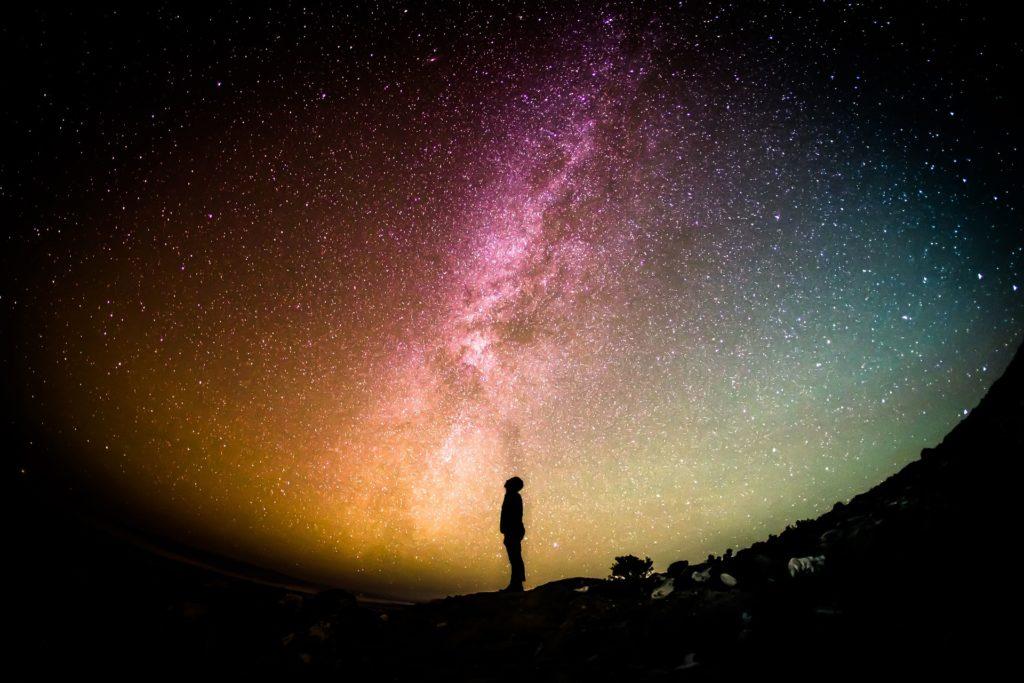 Una persona mira al firmamento, donde se ve la Vía Láctea.