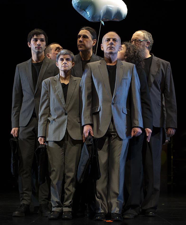Personas vestidas con traje gris se dirijen al frente