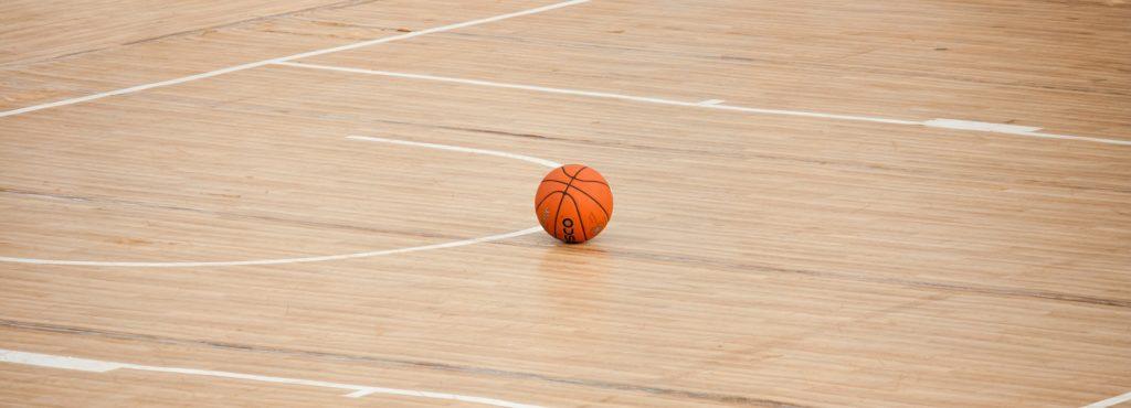 Un balón de baloncesto parado en el suelo de la cancha. No se ve a nadie