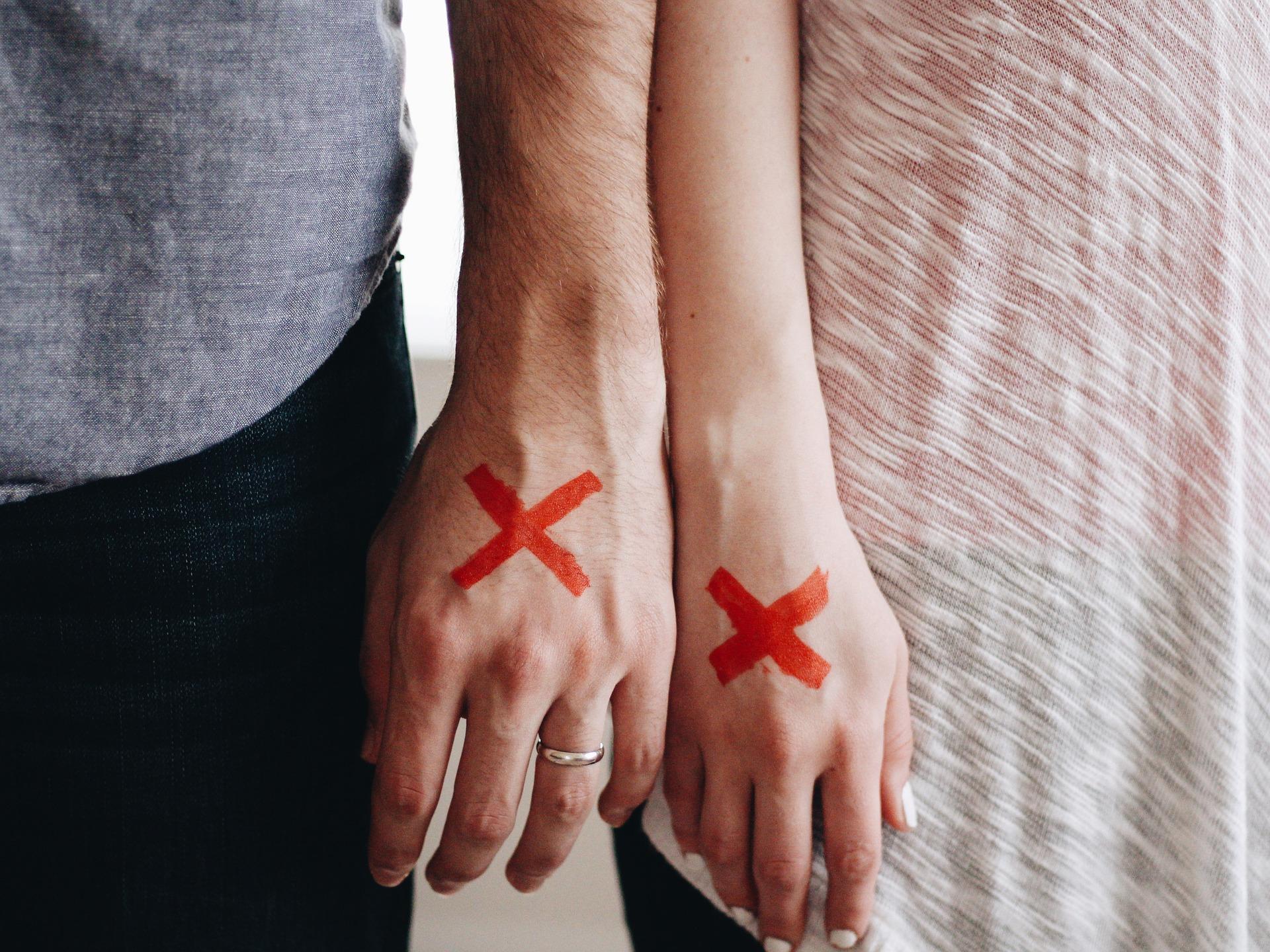 Dos manos, de un hombre y de una mujer, marcadas con una equis en rojo