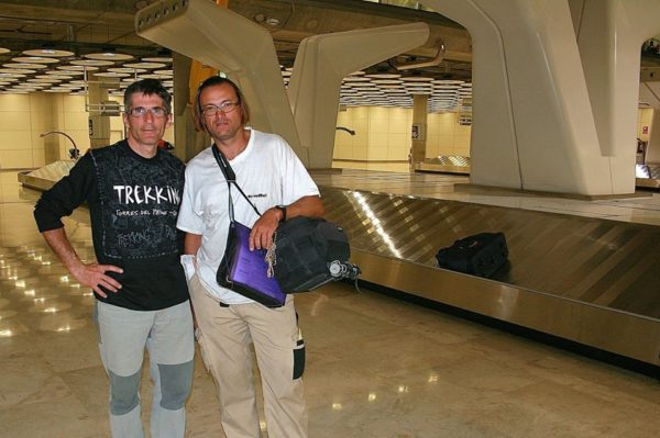 Dos personas en las cintas de recogida de maletas de un aeropuerto