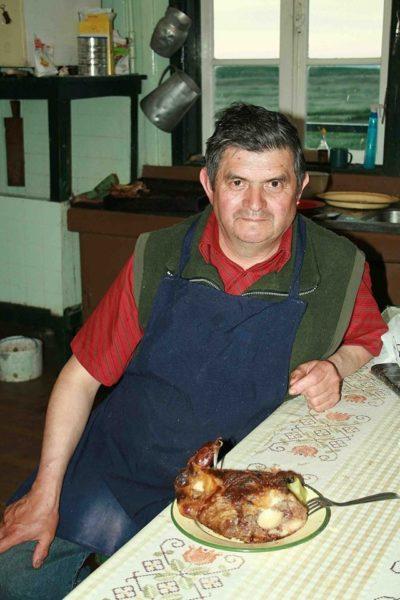 Un hombre sentado en una mesa frente a un asado de carne