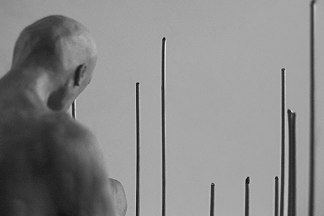 Imagen en blanco y negro de una escultura en arcilla de un hombre. Vemos su hombro y cabeza, y unas verjas verticales
