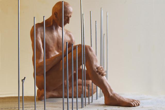 Escultura en arcilla de un hombre sentado que asoma una pierna por una verja