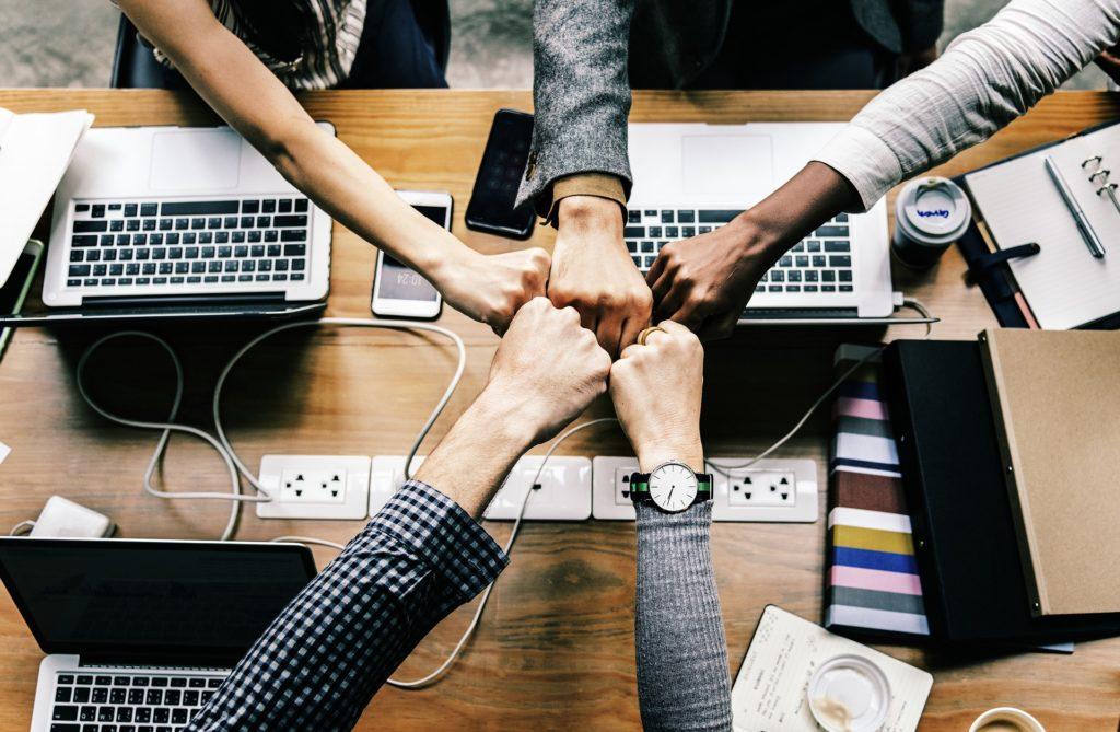 Una mesa de reuniones con ordenadores, cinco manos juntan sus puños en señal de trabajo en equipo