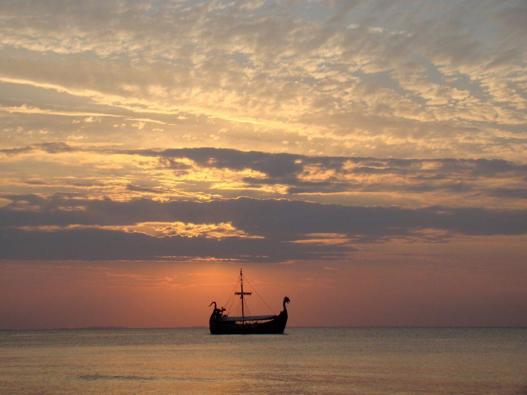 Atardecer en el mar, nave viquinga en la lejanía
