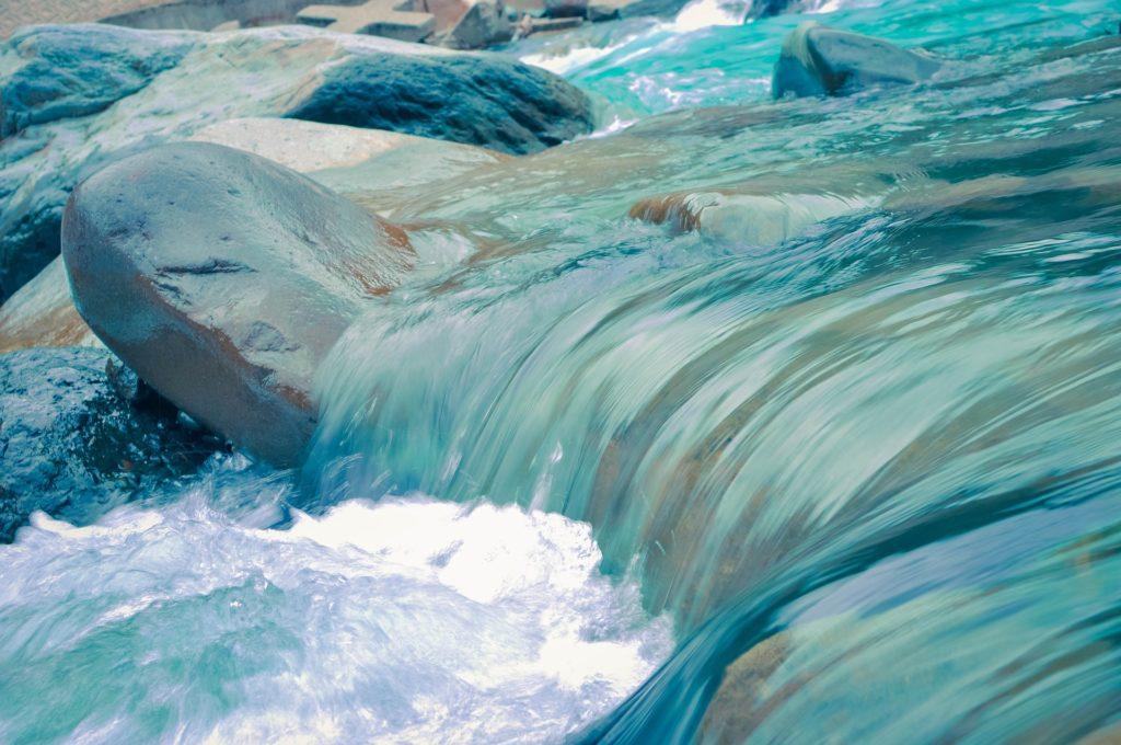 Agua de un río sobre piedras. Color azul intenso, forma un poco de espuma al caer.