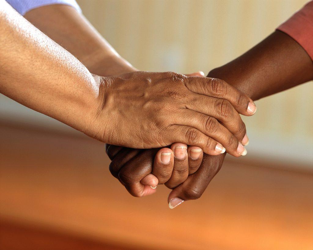 Dos manos de una persona sujetan fraternalmente la mano de otra