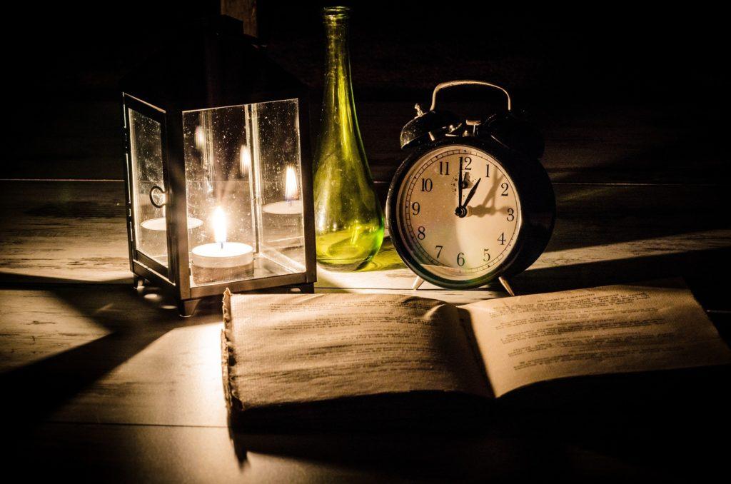 Bodegón con una vela en un farolillo, una botella verde vacía, un despertador antiguo y un libro abierto