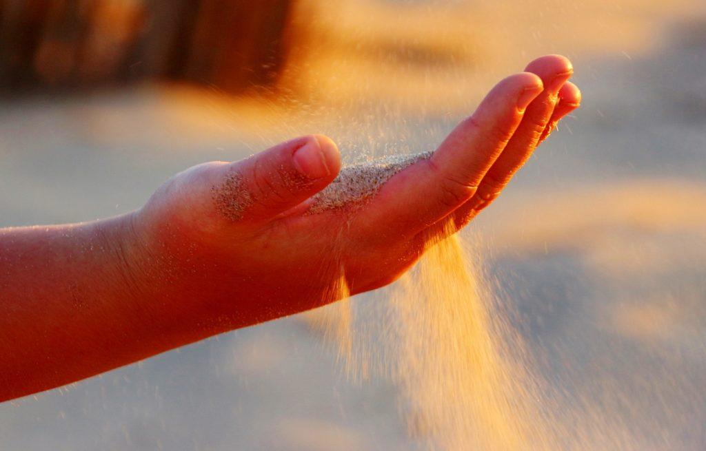 Una mano, entre cuyos dedos se escapa la arena