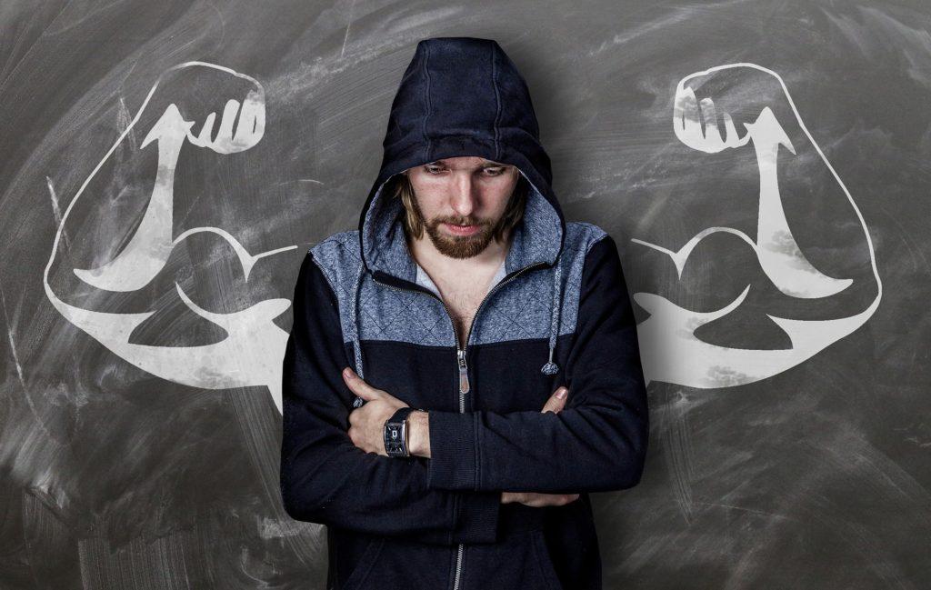 Un hombre con capucha algo triste, frente a una pizarra y con los brazos cruzados. En la pizarra, dibujados unos brazos fuertes y musculosos.