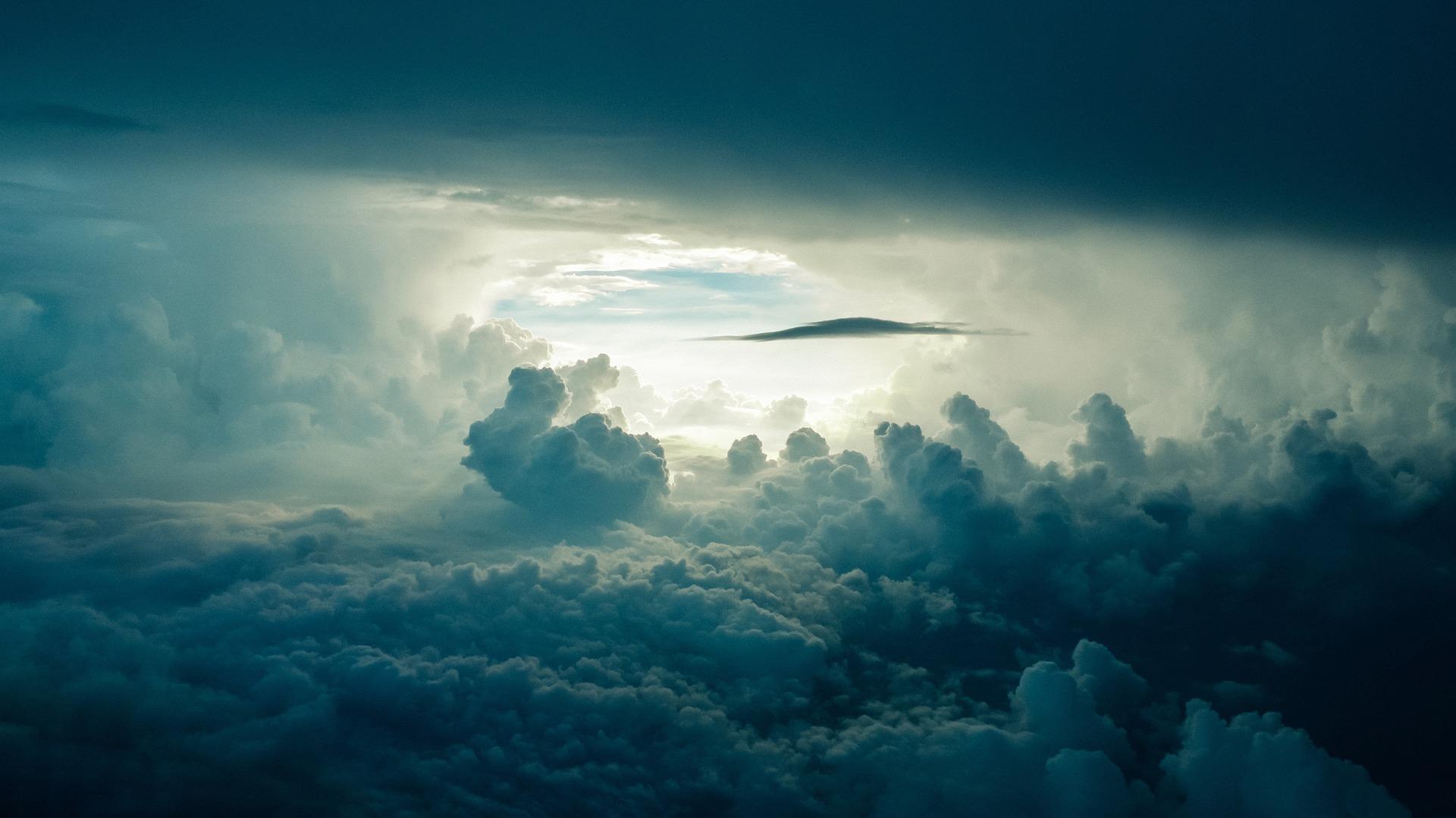 Entre las nubes. Al fondo, un cielo azul se vislumbra en un claro de esas nubes.
