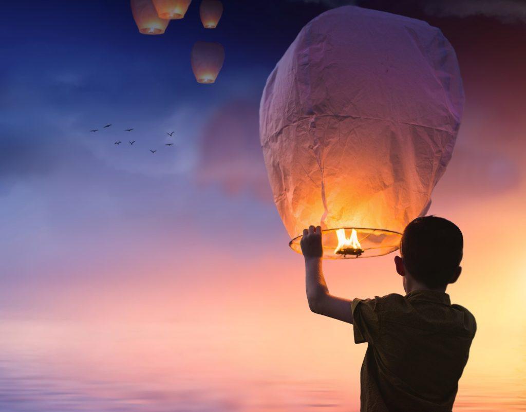Un niño va a soltar un farolillo chino al cielo, donde ya hay otros encendidos volando