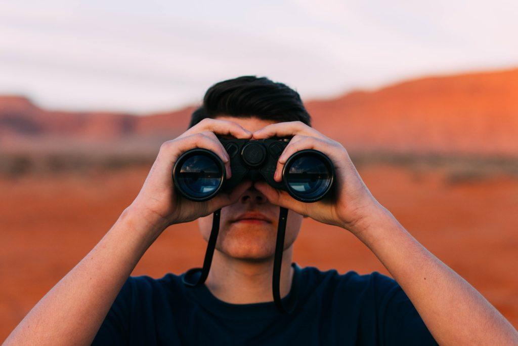 Un hombre mira a través de unos prismáticos. Retrato frontal