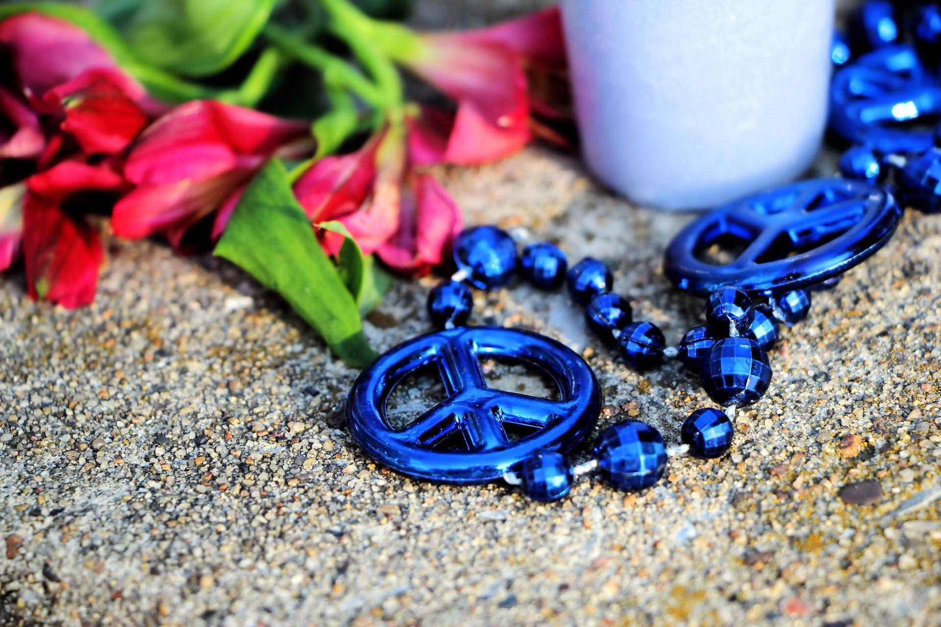 Una vela, unas flores y un cadena azul cuyas cuentas son el símbolo de la paz