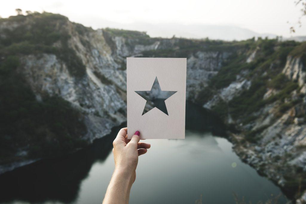 Una mano de mujer sujeta una cartulina en la que hay perforada una estrella, enmarcando un paisaje de roca y un lago al fondo
