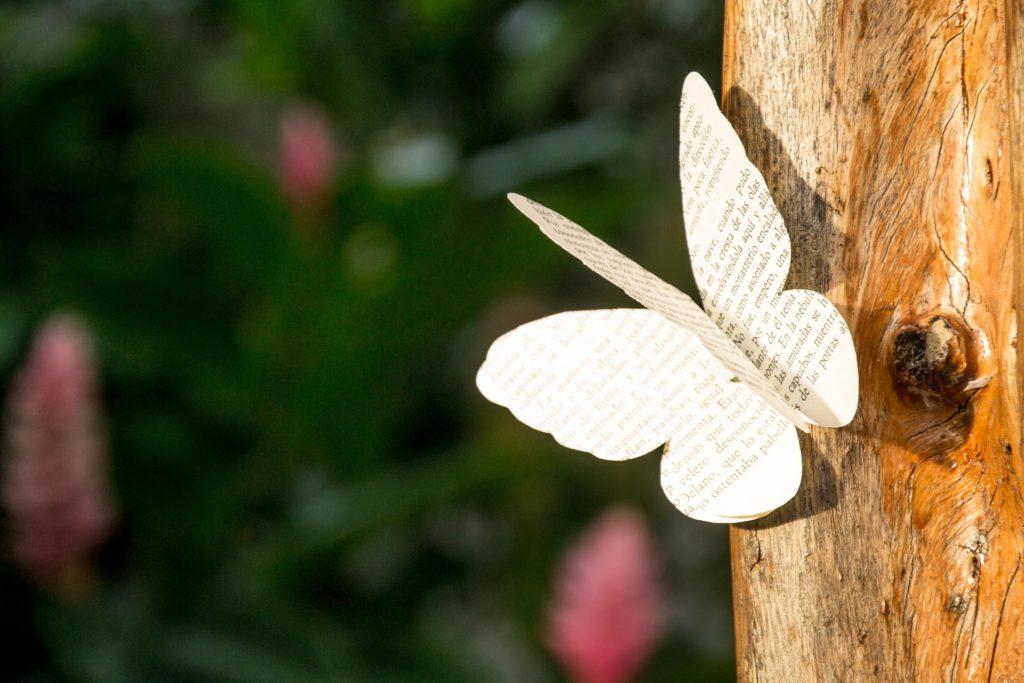 Mariposa hecha con papel de libro, posada en el tronco de un árbol