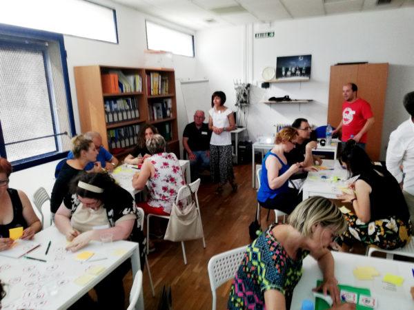 Jornada de socialización en Pamplona. Se ven personas escribiendo en las mesas.