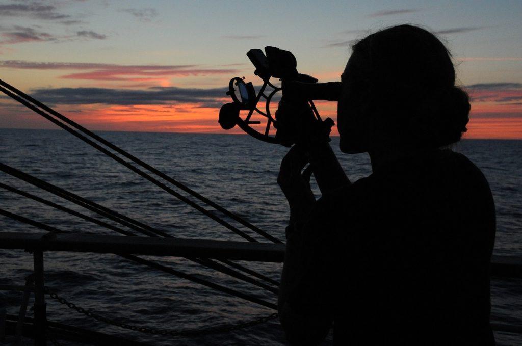 Una mujer utilizando un sextante en el control de mando de un navío