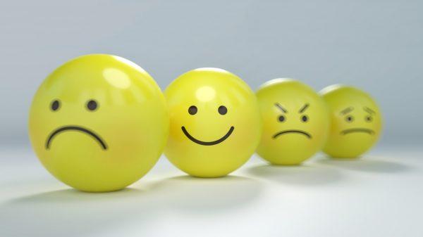 Varios smileys con expresiones enfadadas o tristes, desenfocados. Enfocado únicamente uno con sonrisa.