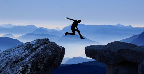 Una persona salta de una roca a otra. De fondo, montañas y niebla