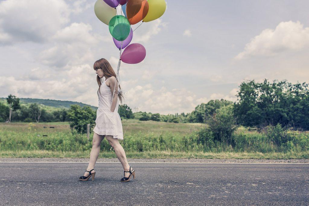Una mujer camina por una carretera en el campo. Del bolsillo de su vestido blanco salen las cuerdas de unos globos de colores, que flotan tras de sí.