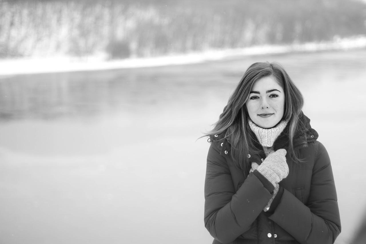 Foto en blanco y negro. Una mujer muy abrigada mira a cámara. Con las manos se cierra el abrigo. Al fondo, una pequeña cascada de agua.