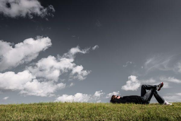 Un hombre tumbado sobre la hierba. Sobre él, un cielo con algunas nubes.