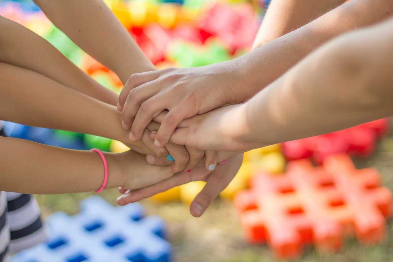 Manos de niños y niñas unidas. El fondo son unos símbolos de almohadilla de colores.