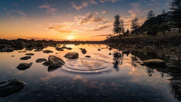 Un río al atardecer, el sol se pone a lo lejos. En la superficie del agua se ven unas ondas.