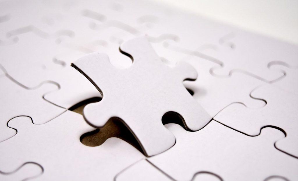 Plano cerrado de un puzzle de piezas blancas. Una última pieza está por caer en su sitio.