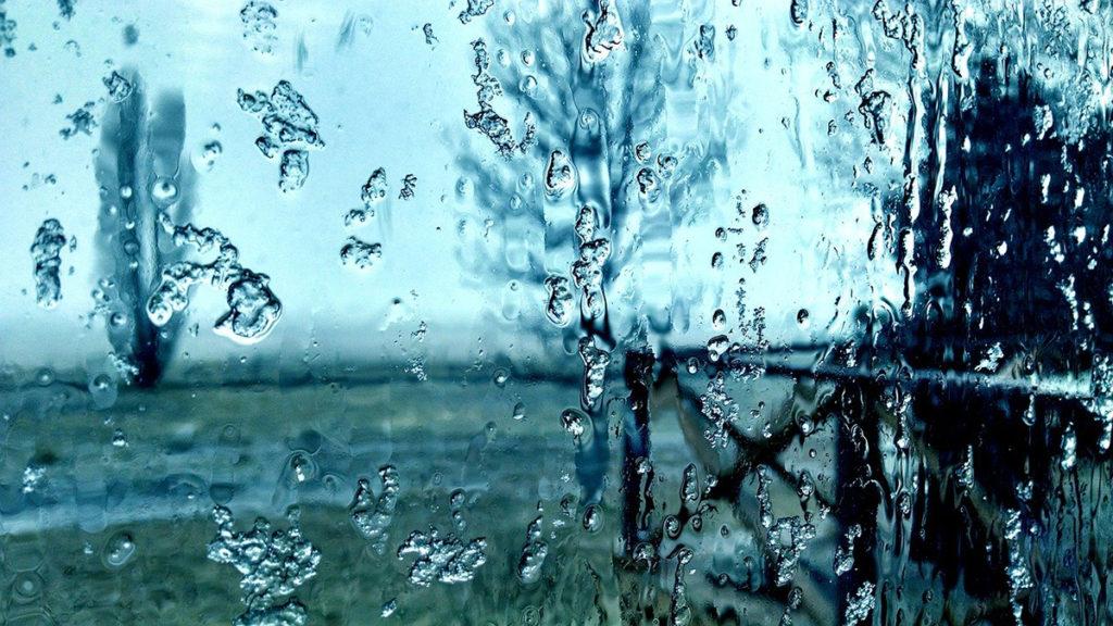 A través de un cristal con hielo derritiéndose, se ven árboles muy borrosos. El tono de la foto es azulado.