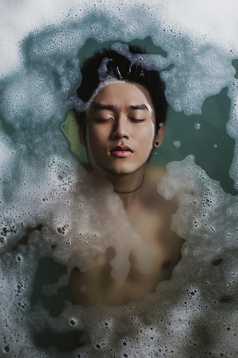 Un chico toma un baño en agua llena de espuma. Lo vemos desde arriba, en plano medio.