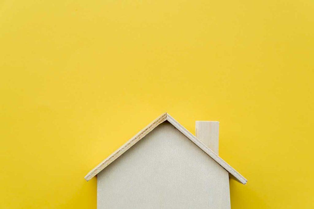 Una casita de madera sobre un fondo amarillo