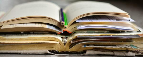 Libros viejos abiertos, uno sobre otro. Entre sus hojas, otras hojas de papel y lápices