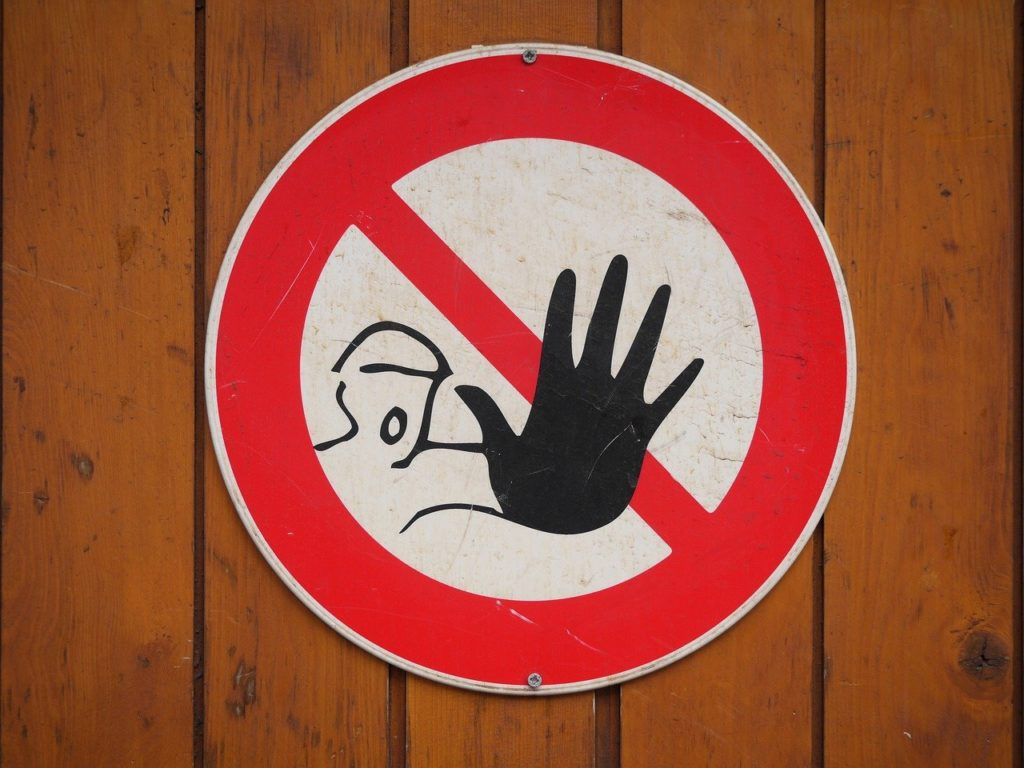 Señal de no seguir, de parar. Es un círculo rojo con una recta en diagonal también en rojo. Desde detrás sale una figura humana dibujada en negro que alza su mano, en primer plano.